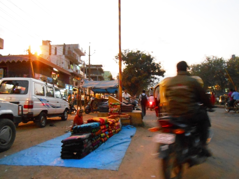 A street vendor selling blankets on a busy street, Bangalore