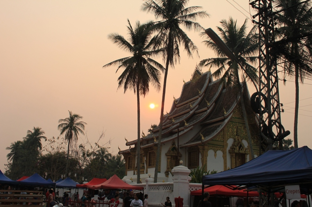 The night market on Sisavangvong Road coming up at dusk with the palace in the background