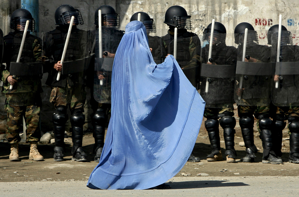 """IMAGE: From boston.com 's The Big Picture feature. Photographer: Ahmad Masood/Reuters . I use this picture for the interesting caption that it appeared with on The Big Picture. These statements end up forming worldview on the country - Continuing conflict, NATO airstrikes and cultural practices combine to make Afghanistan a very dangerous place to be a woman,"""" says Antonella Notari, head of Women Change Makers, a group that supports women social entrepreneurs around the world. A woman walks past riot police outside a gathering in Kabul's stadium, February 23, 2007."""